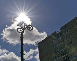 bmx bike leaps from the top of an old telegraph pole, the sun bursts from from a cloud behind against a blue sky. A tenement block sits in the corner of the image
