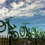 Five green bikes leap from a fence into the sky
