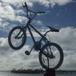 BMX bike 'jumps' into the sky from the top of a pole, overlooking Brighton Pier in the distance