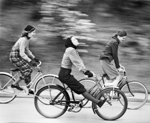 A black & white image of 3 young women speeding along a road on their bikes
