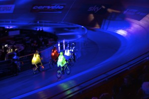5 cyclists in green, red, yellow, white & blue helmets & lit up capes, with lights on their bikes & spokes cycle around a track in an arrow formation
