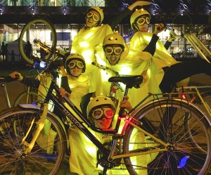 Five performers pose behind a bike with 2 bikes framing either side. Performers are dressed in yellow capes, helmets & goggles with lights underneath the campes on helmets & on the bikes
