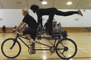 A front rider cycles the tandem and the partially sighted rider on the back, stands on the cross bar, holding the handlebars with one leg raised in the air