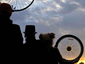 Three silhouetted figures gaze towards the sunset.  Two hold bike wheels and each wears a different hat: a cloche hat with feathers, a top hat, and a furry bear's hat