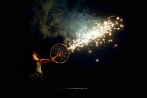 a woman holds a bike wheel shooting a sparkly, gerb firework effect