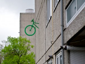 the front wheel and handlebars of a bright green bike emerge from the wall of a block of flats in Roehampton