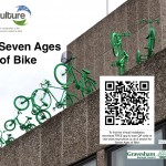 Seven green bikes - from child's bike with stabilisers, to adult's trike - leap from a rooftop. QR code links to www.recyculture.co.uk Search for 'Seven Ages...'