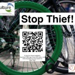 Green wheel padlocked to another bike.  QR code links to www.recyculture.co.uk  Search 'Stop Thief'