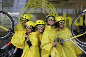 Five performers wearing yellow macs, helmets & goggles pose in between two bikes raised on their back wheels