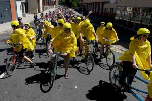 Cyclists stretch down the road in Bristol's CarniVelo ride, fronted by a group on tandems wearning yellow helmets, macs and goggles waving their arms in the air