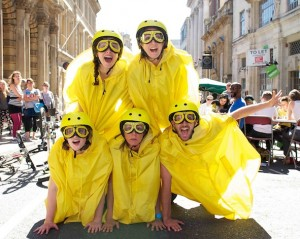 A pyramid of performers costumed in yellow helmets, cycling capes & goggles, backlit by the sun