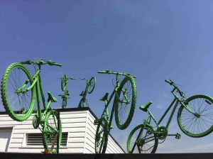 Five green painted bikes, leap from the two roof levels of Putney Leisure Centre